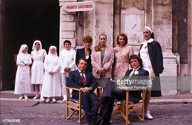 'Group photo of the crew of ''Pronto soccorso 2'' taken on a street the two leading roles are played by Ferruccio and Claudio Amendola seated on...