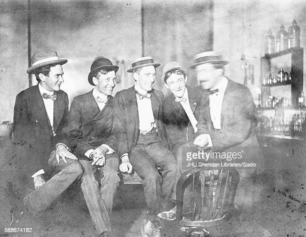 Group photograph of 1901 Johns Hopkins University PhDs in a laboratory wearing skimmer hats and sitting in a row on a table with smiling facial...