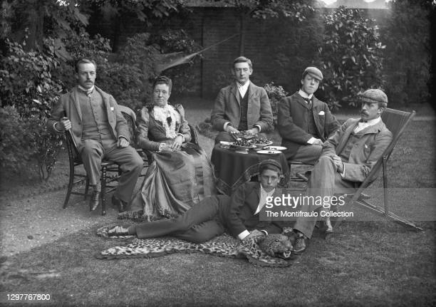 Group photograph of an affluent family seated in a garden the youngest a boy lying on a leopard skin rug England 1890s.