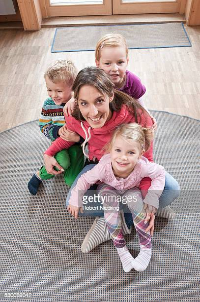 Group picture of female educator and three kids sitting on ground in kindergarten