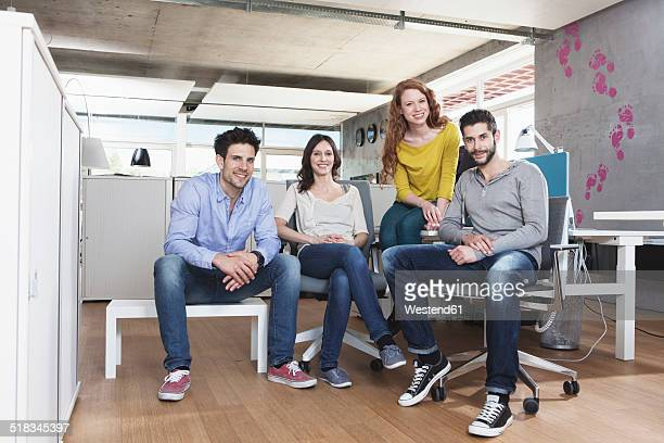 group picture of four creative people sitting in the office - organized group photo stock pictures, royalty-free photos & images