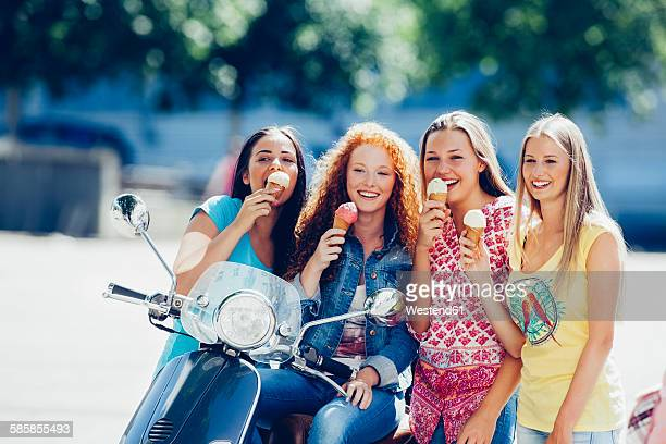 Group picture of four friends with motor scooter and ice cream cones