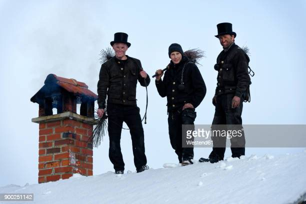 group picture of three chimney sweeps standing on roof top - schornsteinfeger stock-fotos und bilder