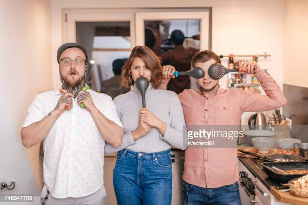 Group picture of three friends having fun with kitchen utensils