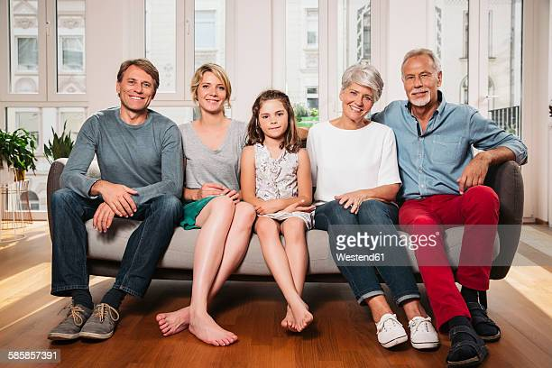 Group picture of three generations family sitting on one couch