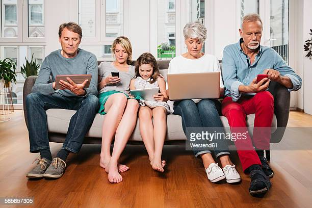 group picture of three generations family sitting on one couch using different digital devices - apparatuur stockfoto's en -beelden