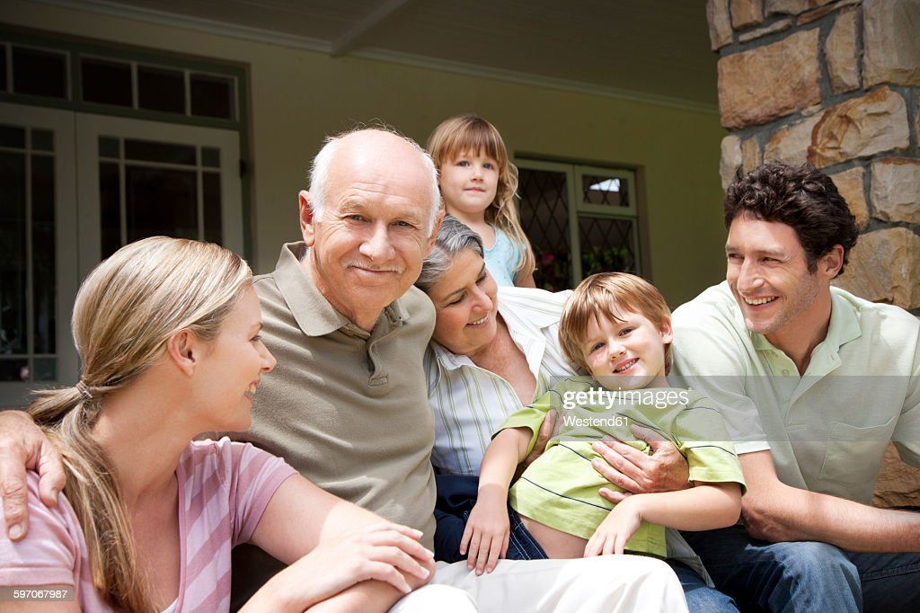 Group picture of three generations family sitting on the terrace : Stock Photo