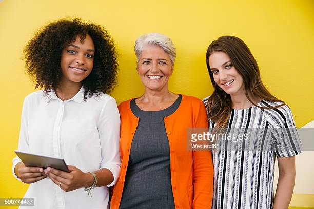 Group picture of three smiling women standing in front of a yellow wall