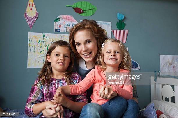 Group picture woman with her little daughters in childrens room