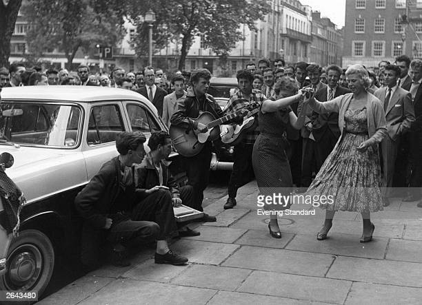 Group playing and jiving in the street at a Fifties fair in Soho, London.