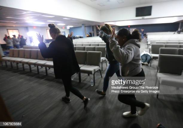 A group playing the roles of victims caught in the middle of gunfire run out of a building during an active shooter training exercise at Bourns in...