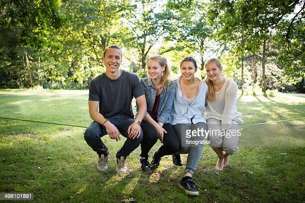 gruppe porträt: freunde sitzen zusammen im park auf der slackline - jugendalter stock-fotos und bilder