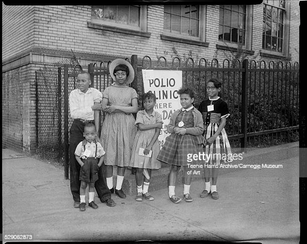 Judy Jackson Arnold Jerry Tyrone Tucker Bertice LaRoach Arlene Roberts and Jo Ann Walker standing in front polio clinic sign on fence at Robert L...