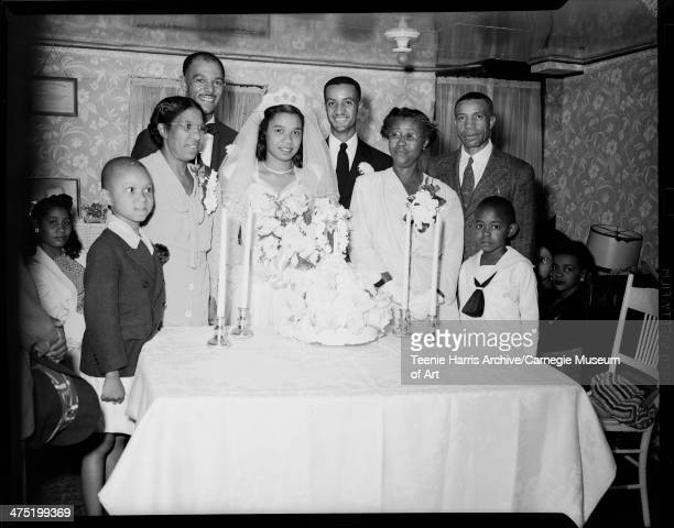 Group portrait Including bride Ruth McDonald Whaley and groom Walter James Whaley posed behind wedding cake in interior with low ceiling and floral...