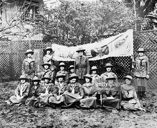 A group portrait of a young women's organisation A banner acroos the back depicts the group's emblems and Juliette Gordon Low stands in the center