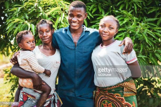 女の子を抱いている彼の2人の妻とアフリカの若者のグループの肖像 - ザンビア ストックフォトと画像