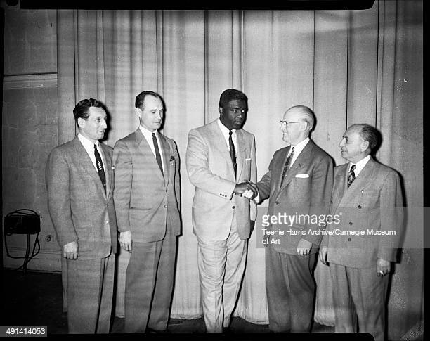 Group portrait of Al Levy Louis A Radelat Jackie Robinson shaking hands with John Maloney and Bert Stern standing in front of curtain Pittsburgh...