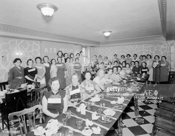 Group portrait of Alpha Epsilon Phi sorority members standing around banquet tables at senior breakfast 22 Langdon Street Madison Wisconsin May 31...