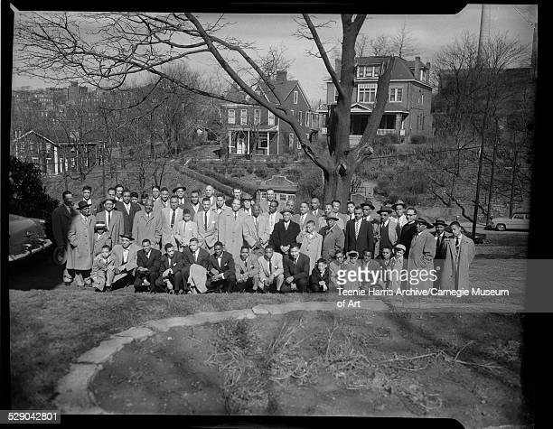 Group portrait of Alpha Phi Alpha fraternity members and boys including Reverend LeRoy Patrick and Robert Goode on right outside with houses on hill...