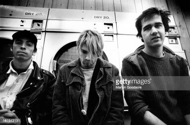 Group portrait of American grunge band Nirvana in a laundrette in Shepherd's Bush London October 1990 LR Dave Grohl Kurt Cobain and Krist Novoselic