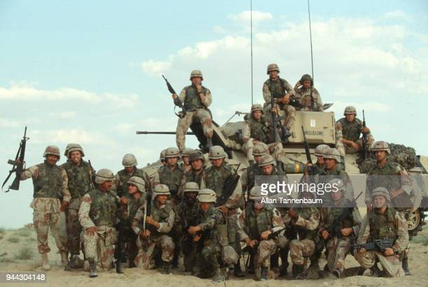 Group portrait of American soldiers as they pose around a Bradley Fighting Vehicle nicknamed 'Hellrazor' during the Gulf War Iraq 1991
