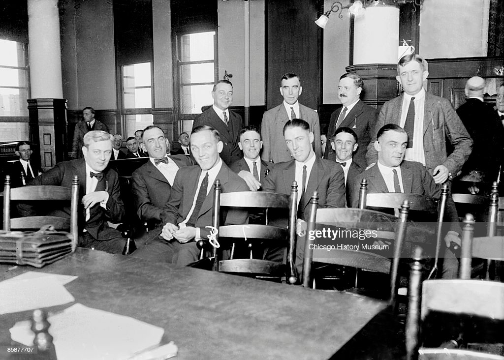 Group portrait of baseball players (left to right) Chick Gandil, Williams, Williams, Charlie Risberg, Eddie Cicotte, George 'Buck' Weaver, and Joe Jackson, of the American League's Chicago White Sox, and attorney Nash sitting in a courtroom in Chicago, Illinois. Attorneys O'Brien and Max Luster and two unidentified men are standing in the background. From the Chicago Daily News collection.