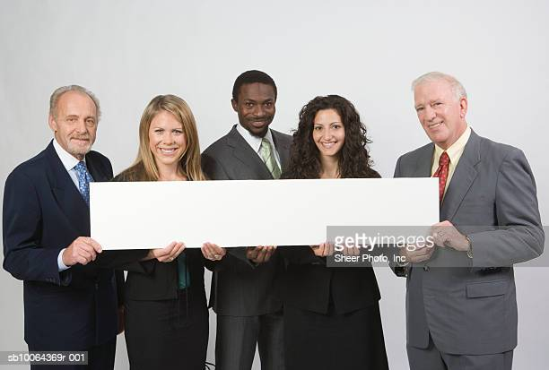 Group portrait of business people holding blank banner