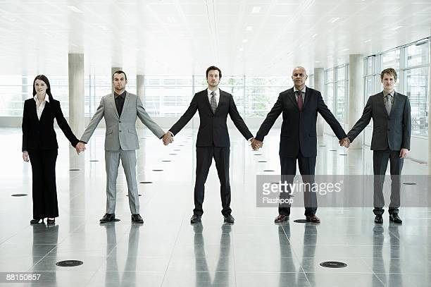 Group portrait of business people holding hands