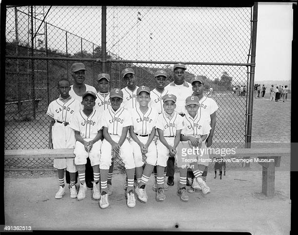 Group portrait of Cardinals 'Cards' Little League baseball team including coach emeritus William Rawls James 'Scotty' Franklin standing in center and...