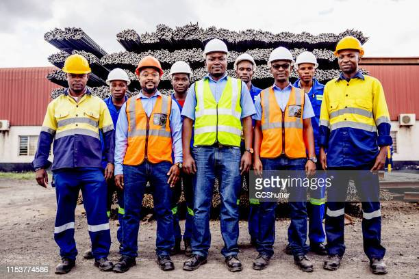 group portrait of confident african steel factory worker team in africa - trade union stock pictures, royalty-free photos & images