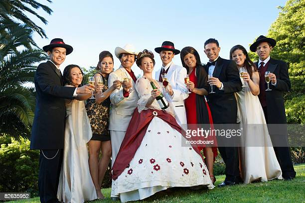Group portrait of couple and guests in garden at Quinceanera