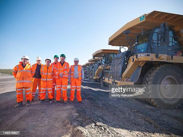 Group portrait of dumper truck drivers standing in opencast coalmine