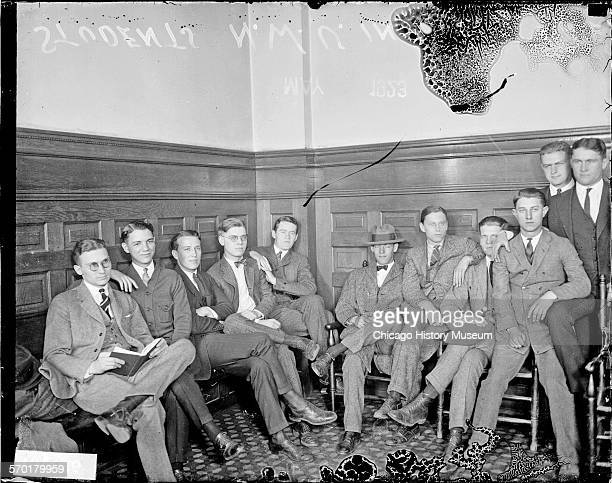 Group portrait of eleven boys students at Northwestern University associated with the hazing murder case of Leighton Mount sitting on benches around...