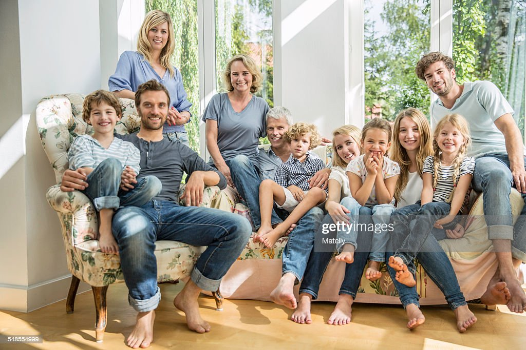 Group Portrait Of Family And Friends Sitting On Sofa In Living Room Stock  Photo | Getty Images