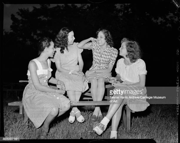 Group portrait of four women including two wearing gingham dresses and one on right wearing saddle shoes gathered around picnic table at North Park...