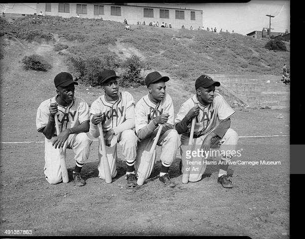 Group portrait of four young men wearing light colored baseball uniforms inscribed 'Kay' posed on one knee and holding baseball bats on field with...