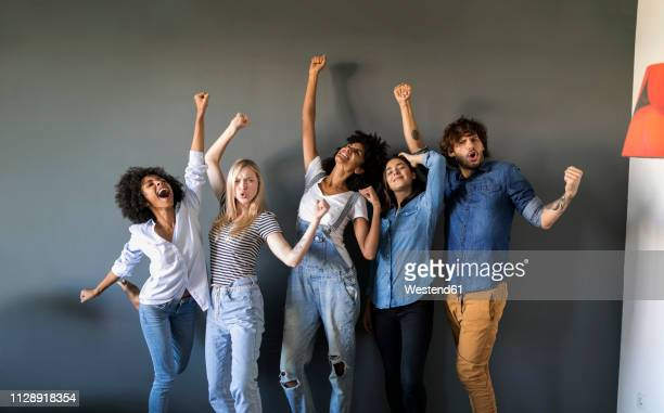 group portrait of friends standing at a wall cheering - organised group photo stock pictures, royalty-free photos & images