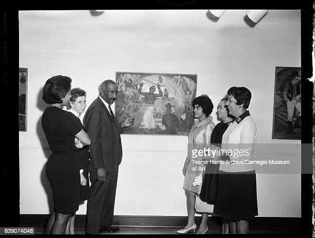 Group portrait of Jo Anne Bates Barbara Hale artist Palmer Hayden standing next to his painting from 'Legend of John Henry' series E Boggs Maxine...