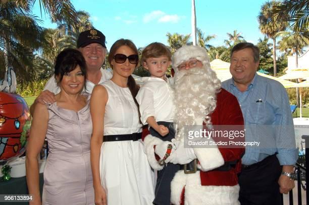 Group portrait of left to right Amalija Knavs Donald Trump Melania Trump Barron Trump Santa Claus and Viktor Knavs on Christmas Day at the MaraLago...