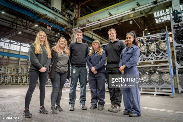 group portrait of male and female apprentices in car factory - オーバーオール ストックフォトと画像