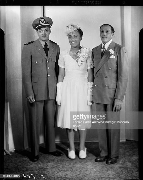 Group portrait of man wearing military uniform bride Hattie Fordham Banks wearing dress with ruched bodice and sweetheart neckline and groom William...