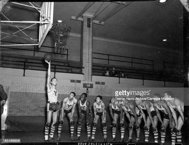 Group portrait of nine male Pittsburgh Y basketball players wearing 'Y Pitt' uniform shirts in Centre Avenue YMCA Pittsburgh Pennsylvania October 1941