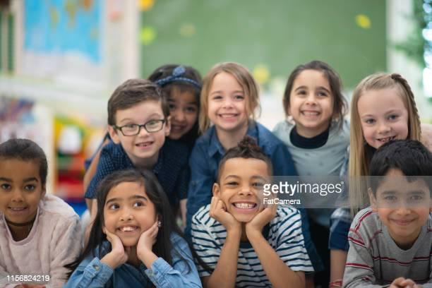 groep portret van glimlachende elementaire kinderen - basisschool stockfoto's en -beelden