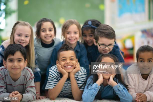 gruppenporträt von lächelnden grundschulkindern - 6 7 jahre stock-fotos und bilder