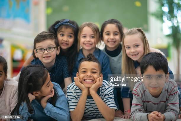 gruppenporträt von lächelnden grundschulkindern - day 6 stock-fotos und bilder