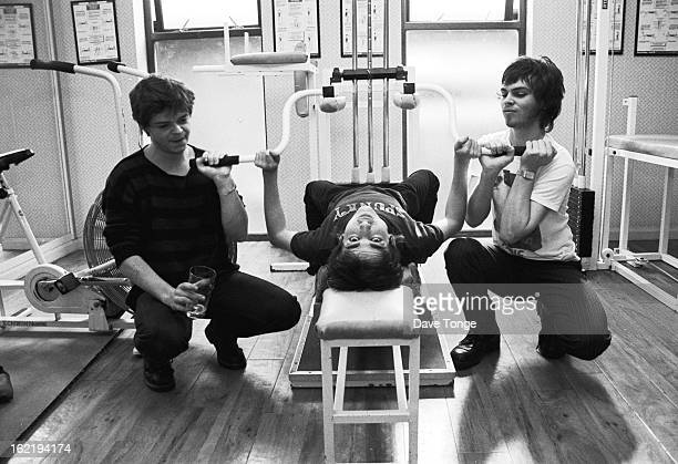 Group portrait of Supergrass in a gym circa 1995. Left to right: Mickey Quinn, Danny Goffey and Gaz Coombes.