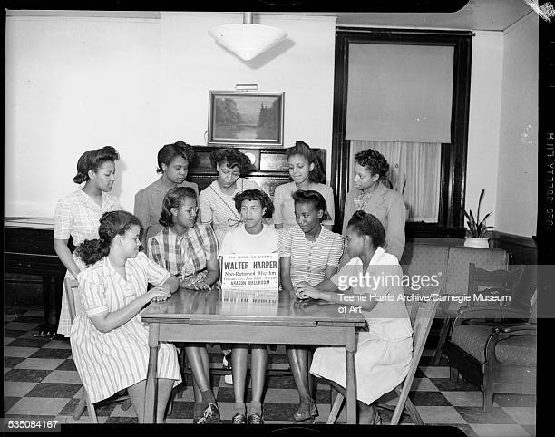 Group portrait of ten women including one in center holding sign inscribed 'The Senior GoGetters Present Walter Harper NonRationed Rhythm Thursday...