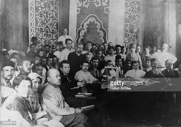Group portrait of the delegates of the Congress of Eastern Peoples posing around a meeting table Baku Azerbaijan American writer John Reed sits next...
