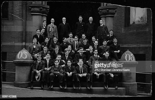 Group portrait of the Johns Hopkins University class of 1905 gathered on the steps to a large brick building in Baltimore, Maryland, 1905. .
