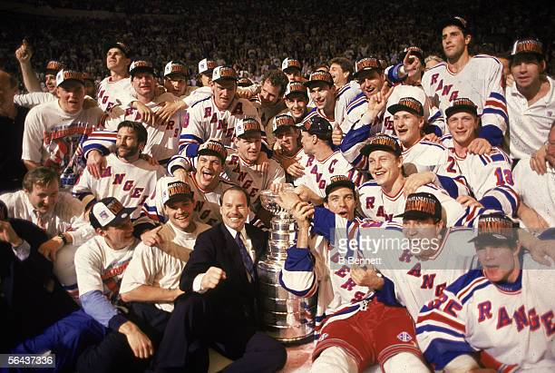 Group portrait of the New York Ranger hockey team on the ice as they pose with the Stanley Cup following their serieswinning defeat of the Vancouver...